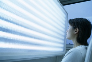 Woman undergoing phototherapy in front of a light screen. Phototherapy is used to treat jet lag.