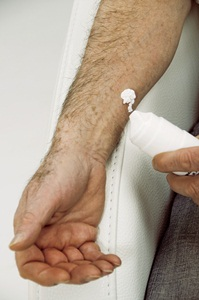 Man applying a skin cream containing <a href='/hormones/testosterone/'>testosterone</a> used to replace this sex hormone in men who have lost their sex drive, or had their <a href='/glands/testes/'>testes</a> removed due to cancer or other diseases.