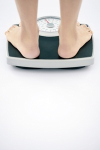 Person standing on weighing scales.
